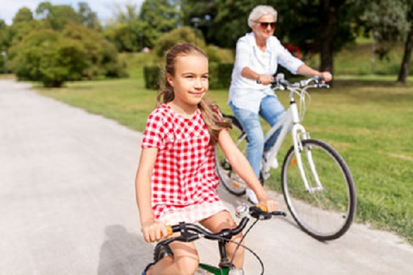 Grandmother riding bike with her granddaughter.